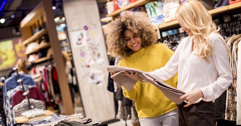 An engaged store associate showing a beige pant to a customer.