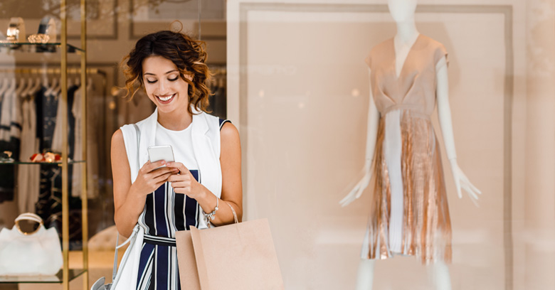 Women shopping online in front of a retail store